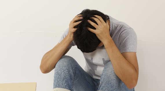 男性が頭を抱えて悩んでいる画像