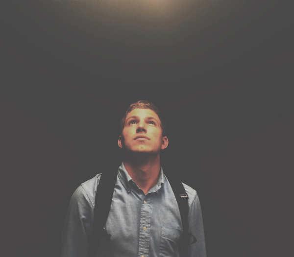 光を見つめる男性