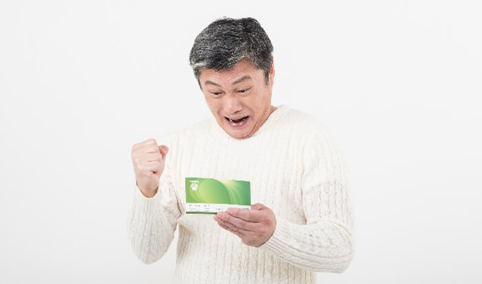 預金通帳を見てガッツポーズをしている男性