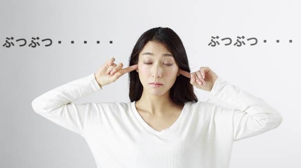 うるさくて耳をふさいでいる女性の写真