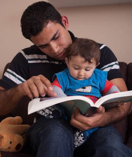 子供に絵本の読み聞かせをしているお父さん