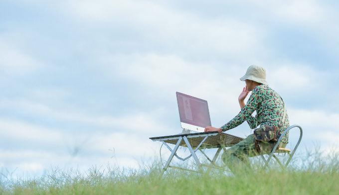 青空の下でパソコンをしている男性の写真