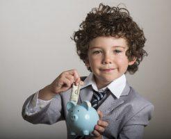 貯金箱にお金を入れている子供