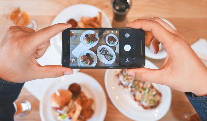 スマホで食べ物の写真を撮っている画像