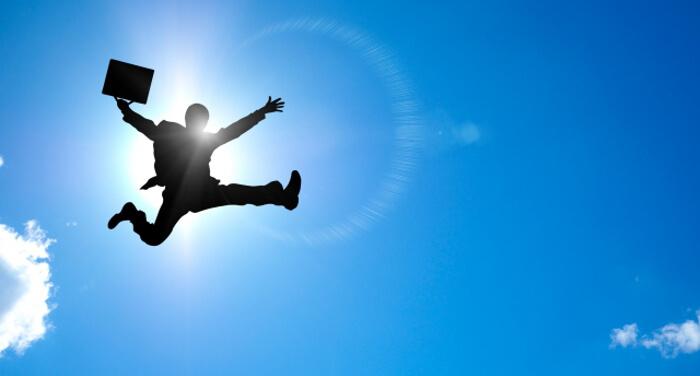 空に向かってジャンプしているサラリーマン