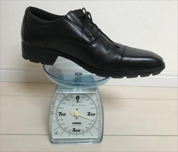 秤でビジネスシューズの重さを測っている写真