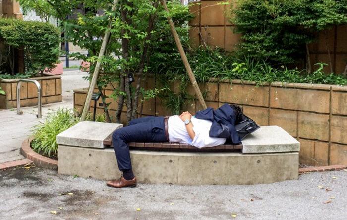 公園のベンチで寝ているサラリーマン