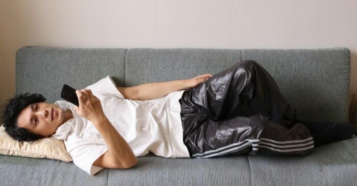 ソファーに寝転がってスマホで映画を観ている男性