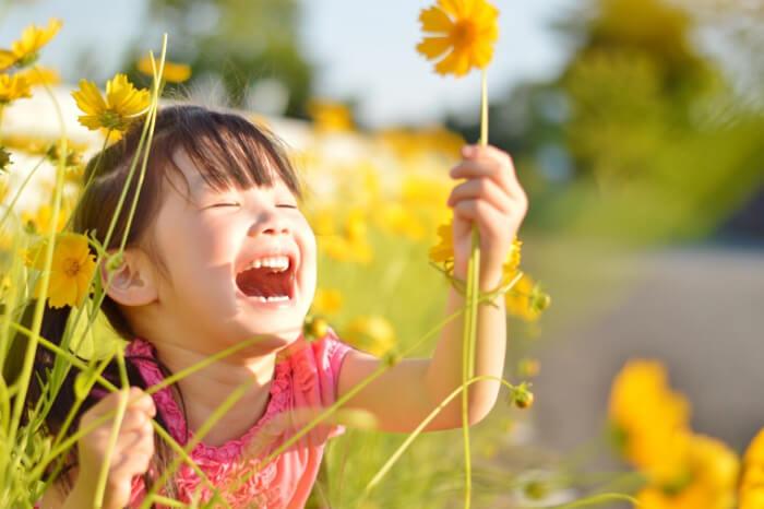 お花畑で子供が笑っている写真