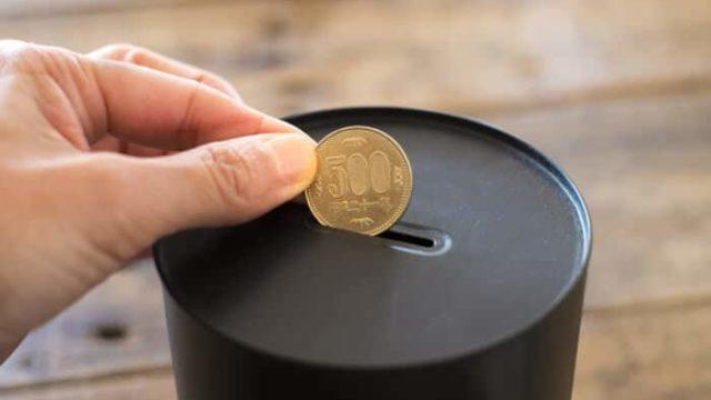 貯金箱に500円玉を入れている写真