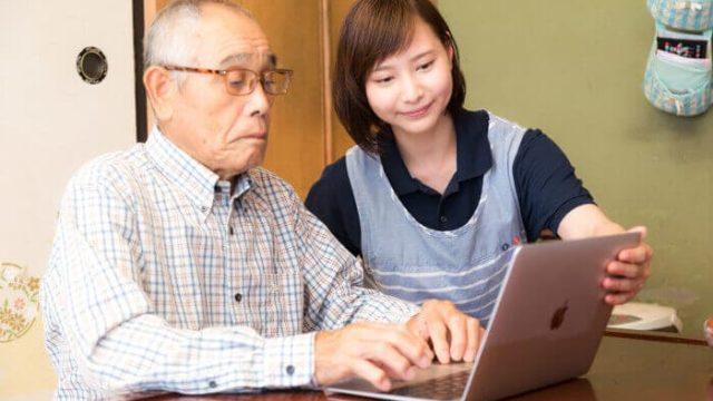高齢者にパソコンを教えている女性