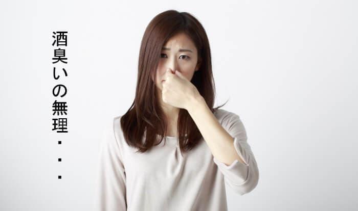 臭いと鼻をつまんでいる女性