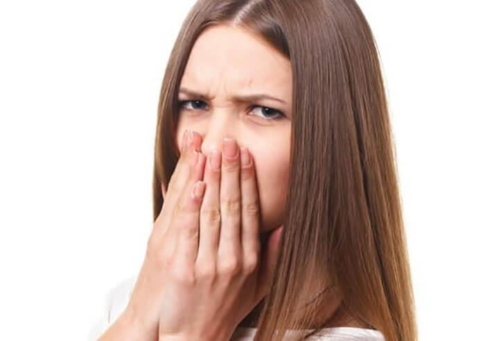 臭くて鼻を抑えている女性