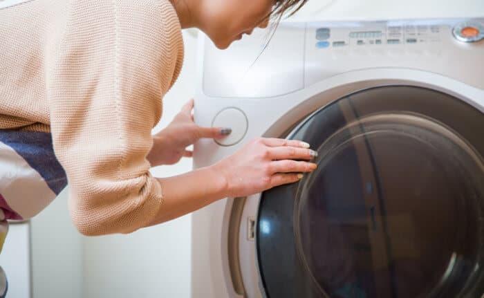 洗濯機の洗濯物を入れている女性
